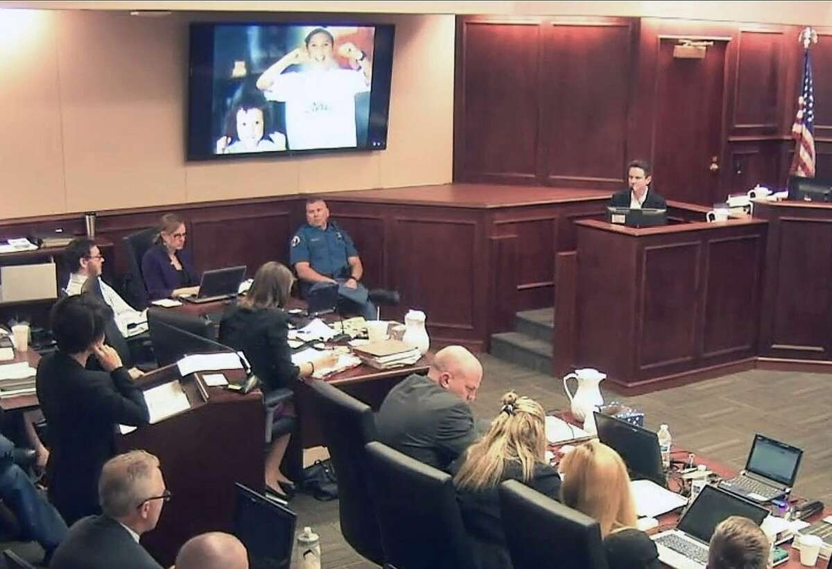 In this image taken from Colorado Judicial Department video, James Holmes, top left in light-colored shirt, sits in court as his younger sister Chris, right, testifies during questioning by Holmes' defense team, in the penalty phase of Holmes' trial, Monday, July 27, 2015, in Centennial, Colo. On the screen above is projected one of several family photos shown during her testimony, this one showing the two siblings smiling and flossing their teeth when they were children. (Colorado Judicial Department via AP, Pool)
