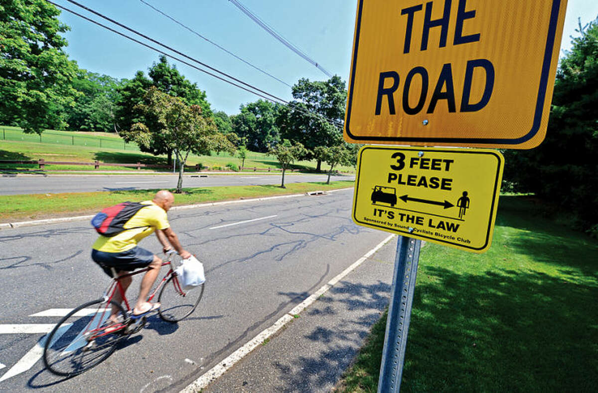 Hour photo / Erik Trautmann The Sound Cyclists Bicycle Club recently donated signs to the City to publicize the CT 3-foot law which mandates motorists allow at least 3 feet of separation when overtaking and passing cyclists.
