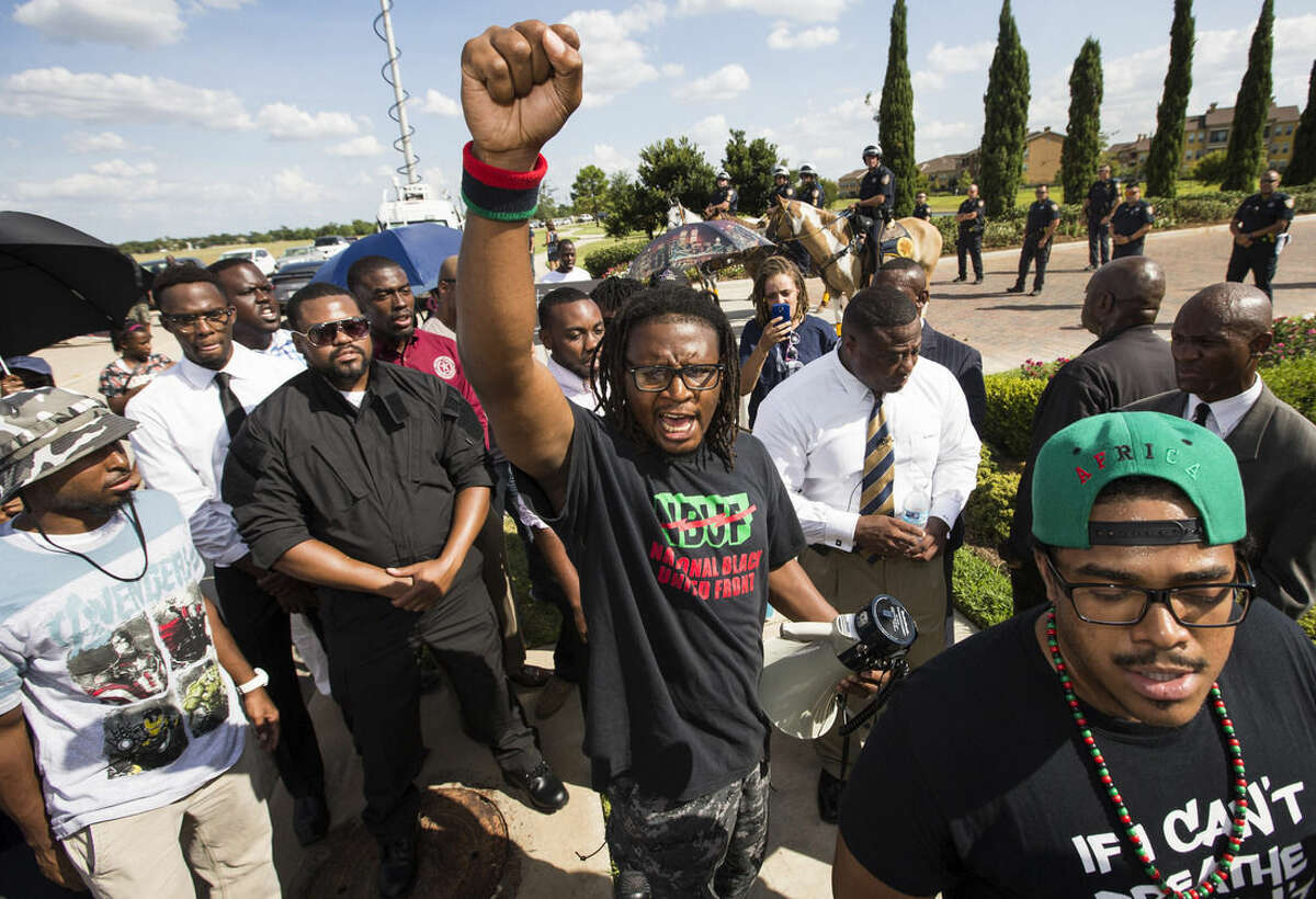 Malik Muhammad raises his fist during a demonstration calling for the firing and indictment of Texas State Trooper Brian Encinia, Sunday, July 26, 2015, in Katy, Texas. Sandra Bland was found dead in her cell on July 13 in the Waller County Jail, just days after being arrested by Encinia during a traffic stop. Authorities determined through an autopsy that Bland hanged herself with a plastic bag. (Brett Coomer/Houston Chronicle via AP)