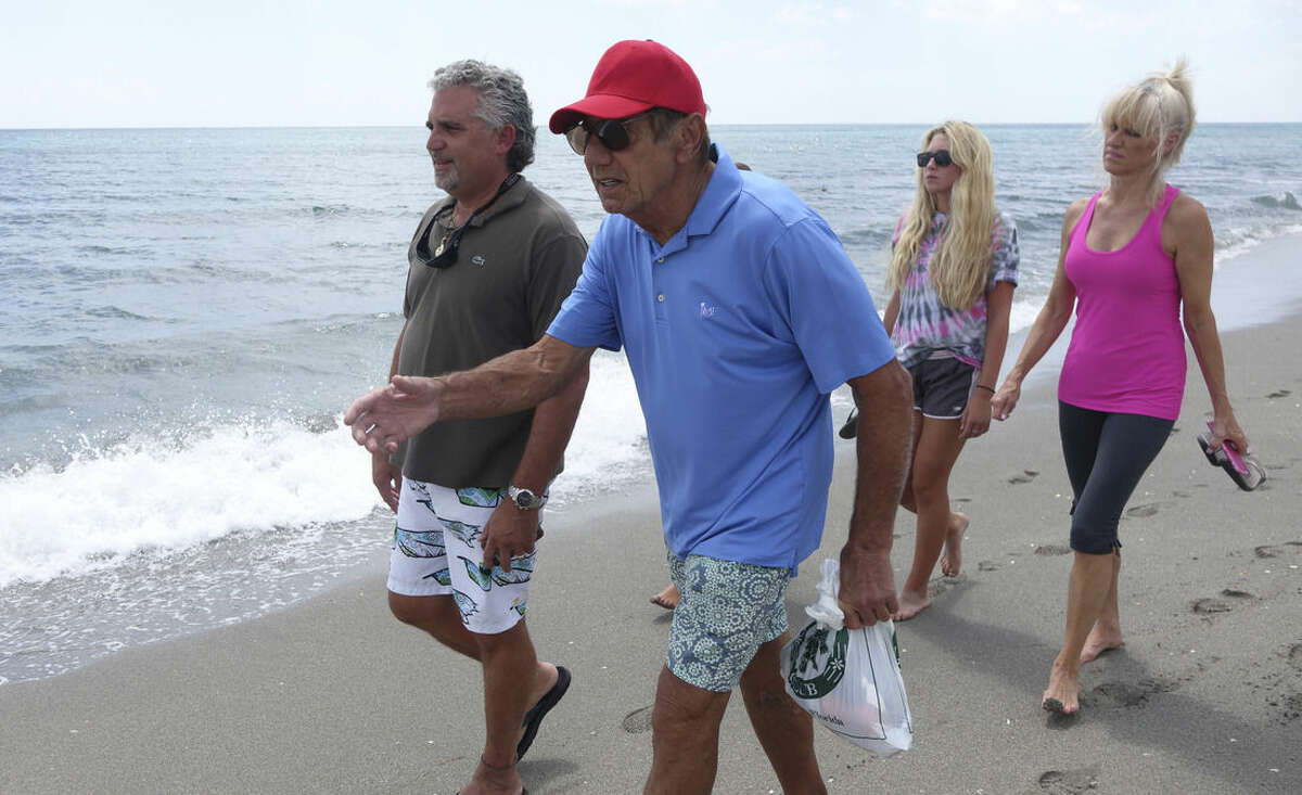 Former NFL great and Tequesta, Fla. resident Joe Namath, front left, walks the beach at Coral Cove Park in Jupiter, Fla., searching for possible clues washed up, Monday, July 27, 2015 with the family of one of two teenage fishermen who went missing three days earlier after setting out for the Bahamas. The family is asking for help along the shore for locating any items that might have drifted when the teen's boat capsized. (Joe Cavaretta/South Florida Sun-Sentinel via AP) MAGS OUT; MANDATORY CREDIT