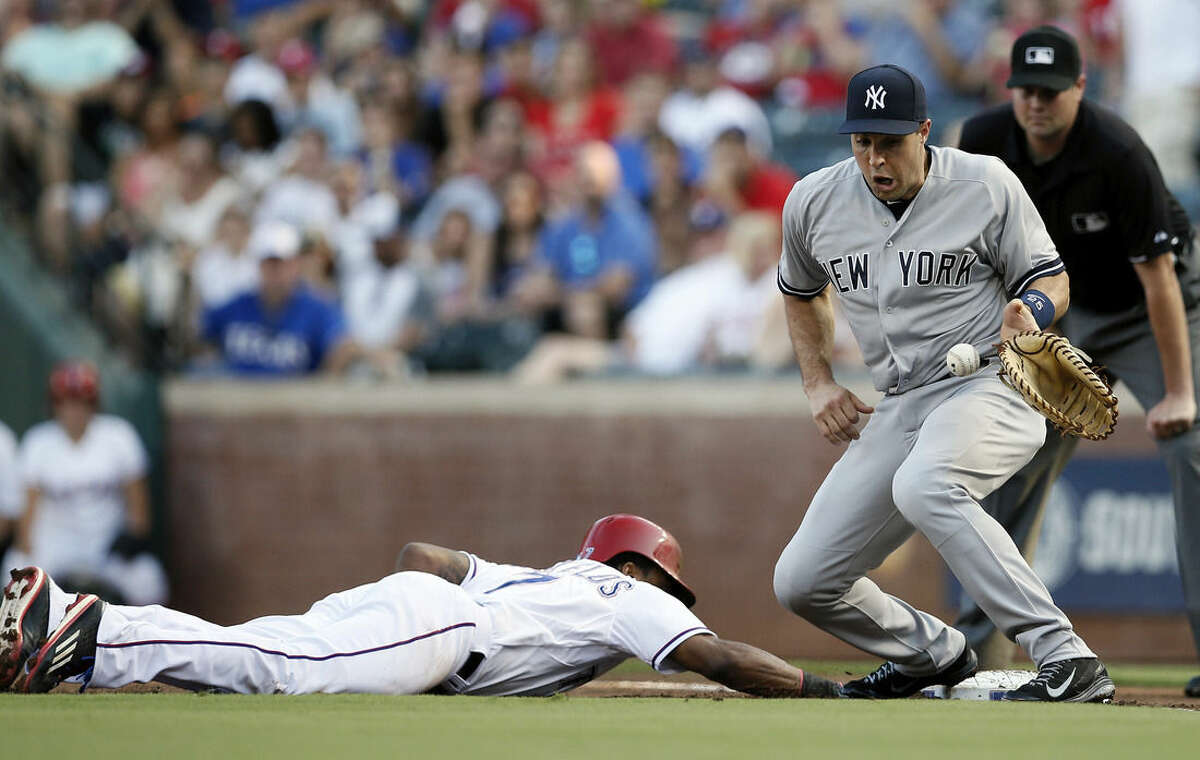 New York Yankees first baseman Mark Teixeira bobbles to throw from pitcher Chris Capuano as Texas Rangers' Delino DeShields gets back to first safely on a pick off attempt in the first inning of a baseball game Tuesday, July 28, 2015, in Arlington, Texas. (AP Photo/Tony Gutierrez)