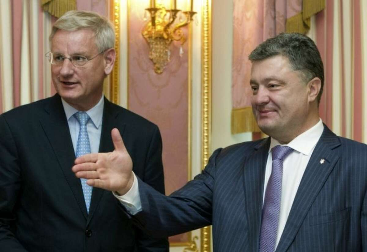 Ukrainian President Petro Poroshenko, right, greets Swedish Foreign Minister Carl Bildt during their meeting in Kiev, Ukraine, Tuesday, July 1, 2014. Ukrainian forces and pro-Russian separatists fought with heavy weapons in the country?'s east Tuesday, and the rebels captured the Interior Ministry headquarters in a major city after an hours-long gun battle, a day after the president said rebels weren?'t serious about peace talks and ended a cease-fire. (AP Photo/Presidential Press Service, Mykhailo Markiv, Pool)