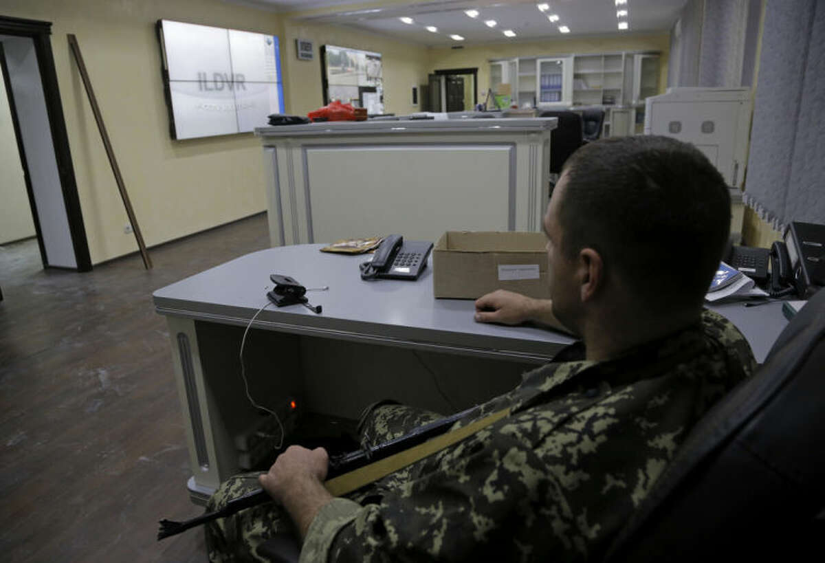 A pro-Russian fighter sits at the duty department of the captured Interior Ministry headquarters in Donetsk, eastern Ukraine Tuesday, July 1, 2014. The rebels captured the Interior Ministry headquarters in the city after an hours-long gun battle, a day after the president said rebels weren't serious about peace talks and ended a cease-fire. (AP Photo/Dmitry Lovetsky)
