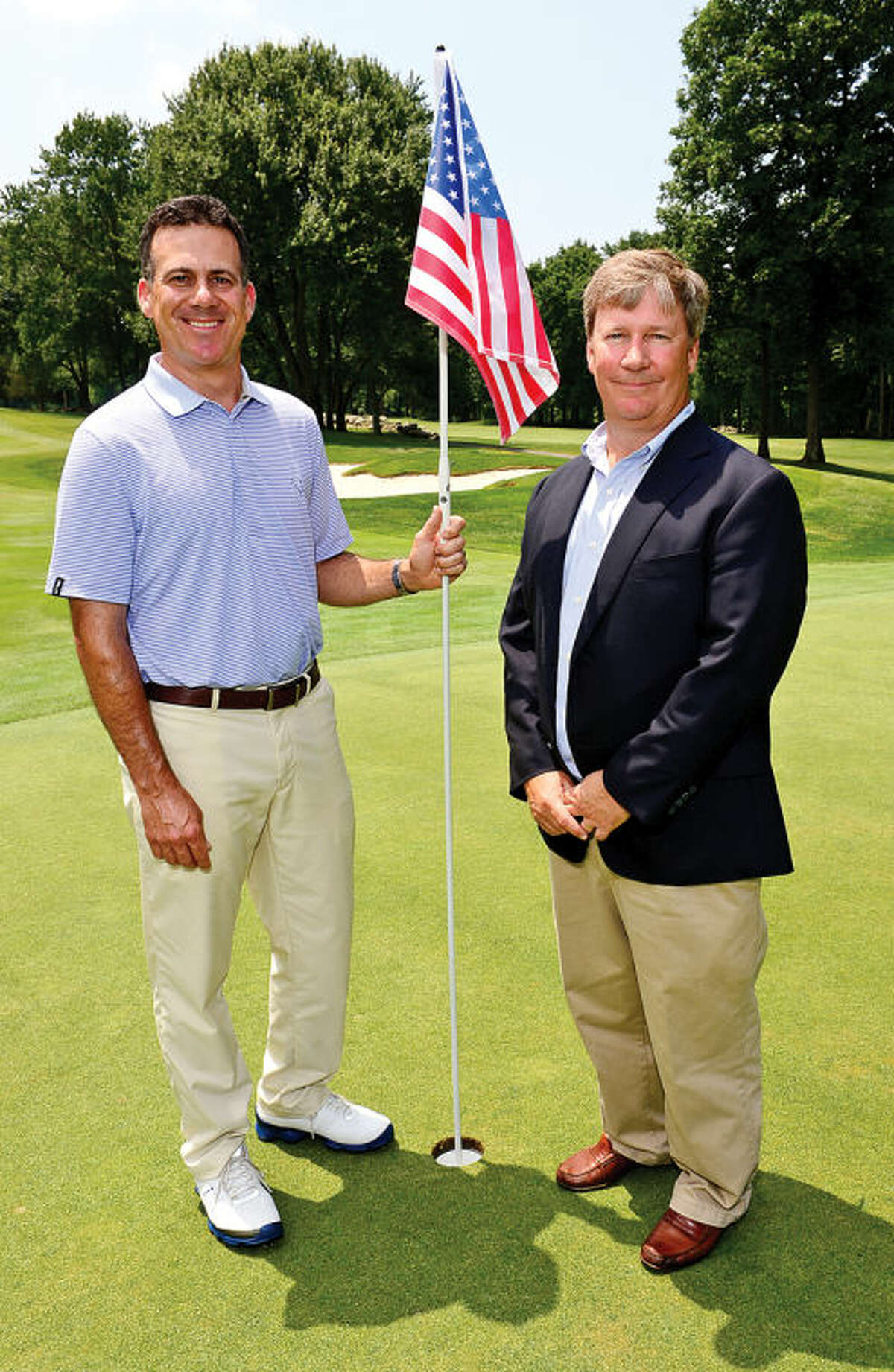 Hour photo / Erik Trautmann Rolling Hills Country Club's golf pro Ray Ford and club president Tim Mahon pose on the 18th greeen after they held a press conference/media day announcing the upcoming Connecticut Open Golf Championship Wednesday.