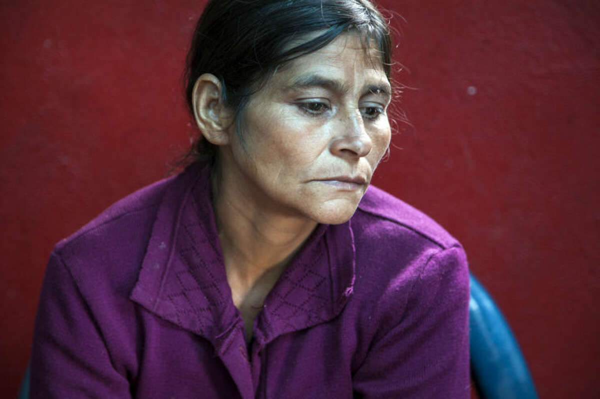 Cipriana Juarez Diaz, mother of Gilberto Francisco Ramos Juarez, a Guatemalan boy whose decomposed body was found in the Rio Grande Valley of South Texas, listens to her husband talk, during an interview at their home in San Jose Las Flores, in the northern Cuchumatanes mountains of Guatemala, Tuesday, July 1, 2014. Juarez Diaz said that she begged her son not set out on the dangerous journey from their modest cinder block- and sheet-metal home high in the northern Guatemalan mountains. (AP Photo/Luis Soto)