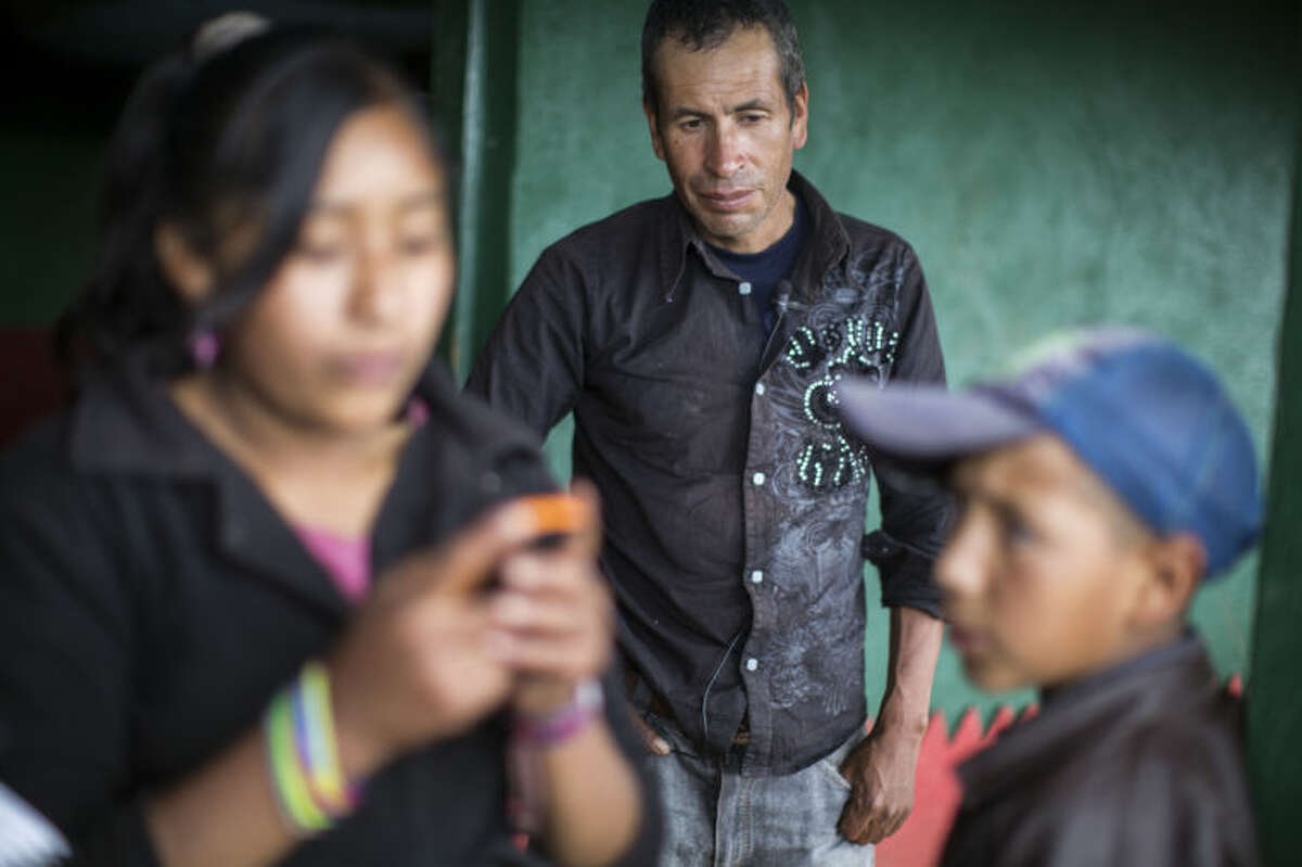 Francisco Ramos Diaz, center, father of Gilberto Francisco Ramos Juarez, a Guatemalan boy whose decomposed body was found in the Rio Grande Valley of South Texas, looks on as a neighbor answers a call, at his home in San Jose Las Flores, in the northern Cuchumatanes mountains of Guatemala, Tuesday, July 1, 2014. The boy's birth certificate says he was 11 years old, but his father said Tuesday that the boy was really 15. (AP Photo/Luis Soto)