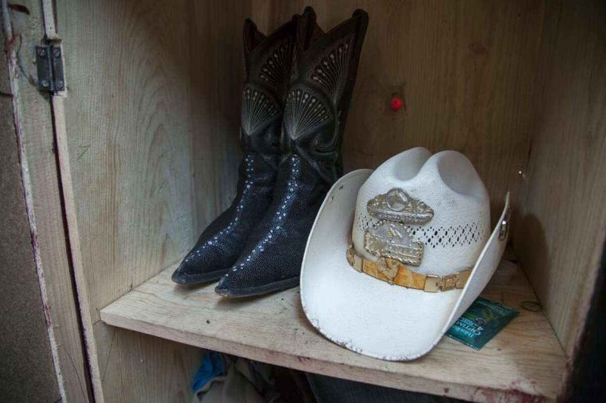 A pair of boots and a hat belonging to Francisco Ramos Juarez, a Guatemalan boy whose decomposed body was found in the Rio Grande Valley of South Texas, are shown inside a closet at his home in San Jose Las Flores, northern Cuchumatanes mountains, Guatemala, Tuesday, July 1, 2014. The boy was found with the rosary still around his neck and a brother's Chicago phone number scribbled on the inside of his belt buckle about two weeks ago. He was alone in brush less than a mile from the nearest U.S. home, a South Texas sheriff said Monday. (AP Photo/Luis Soto)