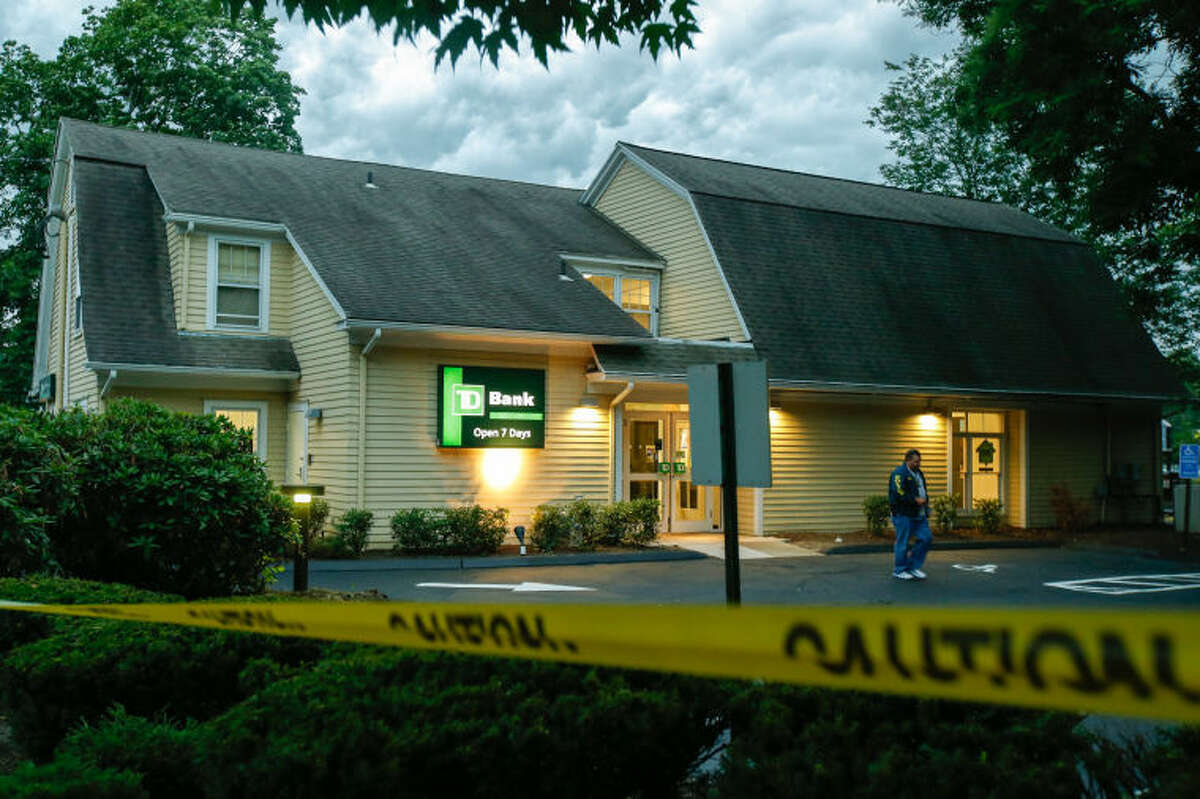 Hour photo/Chris Palermo. A Westport police officer walks out of the TD Bank at 1111 Post Road East in Westport after the bank was held up Wednesday afternoon.