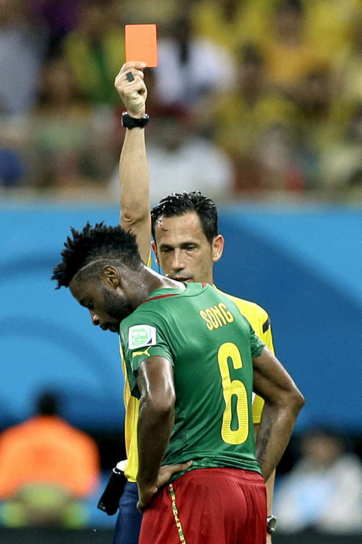 FILE - In this Wednesday, June 18, 2014 file photo, referee Pedro Proenca from Portugal gives a red card to Cameroon's Alex Song during the group A World Cup soccer match between Cameroon and Croatia at the Arena da Amazonia in Manaus, Brazil. Cameroon's football federation said late Monday, June 30, 2014, it will investigate allegations of match-fixing by its team at the World Cup and the possible existence of