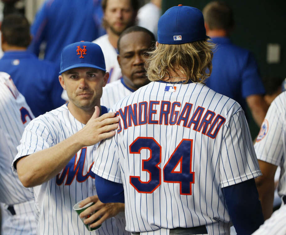 New York Mets David Wright, left, pats New York Mets starting pitcher Noah Syndergaard (34) on the back as they pass between the first and second innings in the dugout during a baseball game against the San Diego Padres in New York, Tuesday, July 28, 2015. Wright participated in a brief workout Tuesday after he was cleared to resume baseball activities coming off the DL. (AP Photo/Kathy Willens)