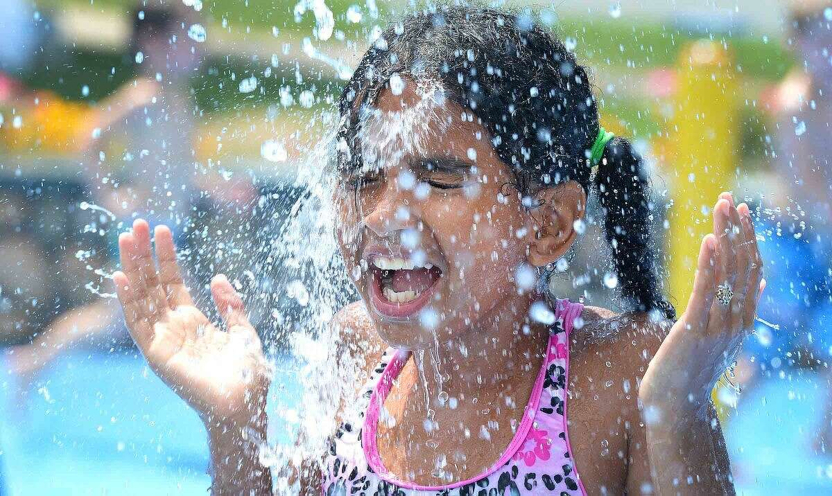 Hour Photo/Alex von Kleydorff 9yr old Cristal Baez gets splashed with a bucket of water at Norwalk's Calf Pasture Beach Splash Pad on Wednesday. With temperatures in the 90's for the the third consecutive day, area residents have a place to cool off and have fun during the heat wave