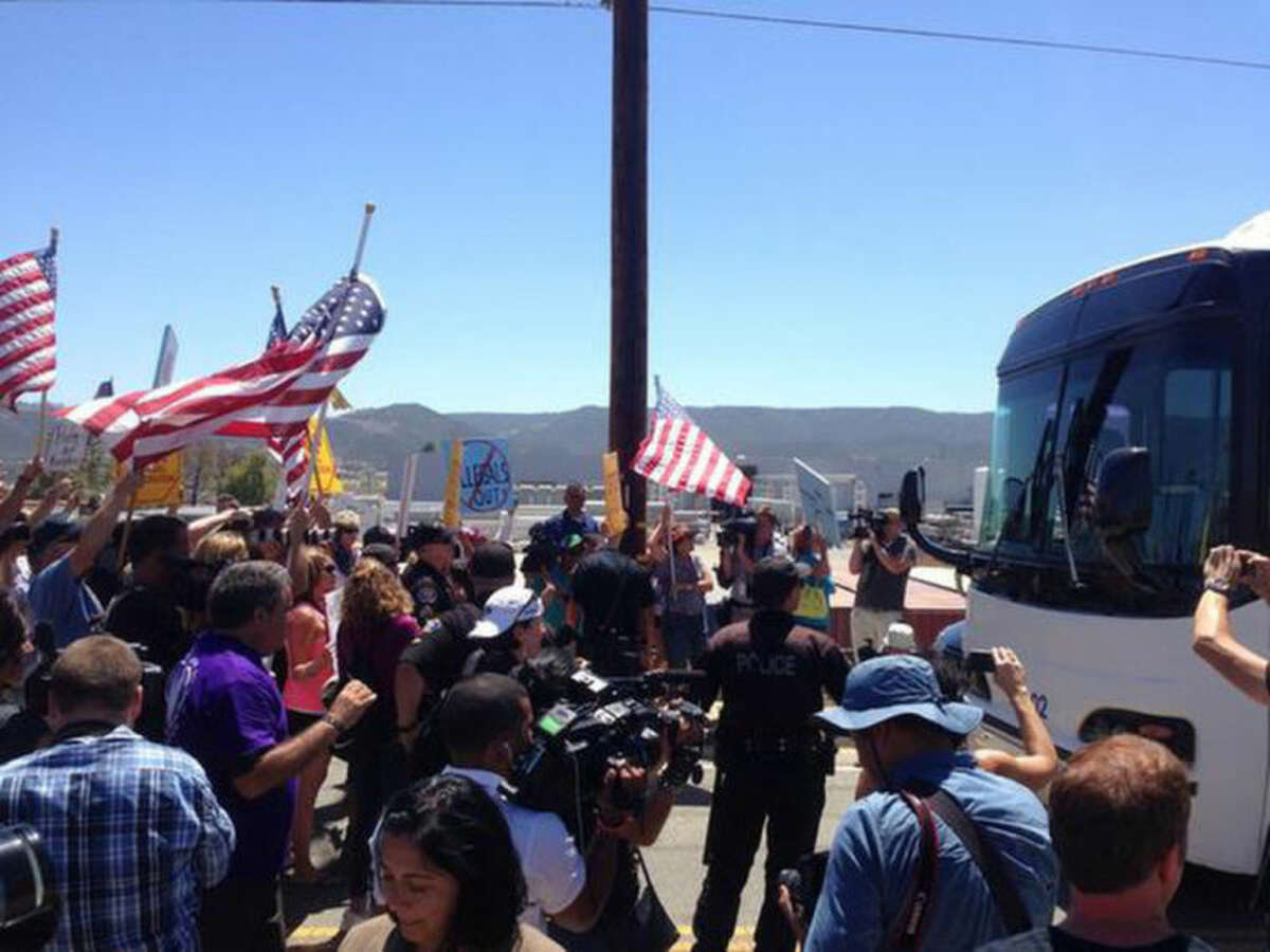 Protesters stand in the road blocking a bus carrying 140 immigrants on the way to be processed at the Murrieta border patrol station on Tuesday, July 1, 2014. The immigrants are bused to a border patrol facility in Murrieta, about an hour north of San Diego, for processing. Federal immigration authorities there will determine whether they will be held or released pending deportation proceedings.(AP Photo/The Press-Enterprise, Sarah Burge) (AP Photo/The Press-Enterprise, ) MAGS OUT; MANDATORY CREDIT