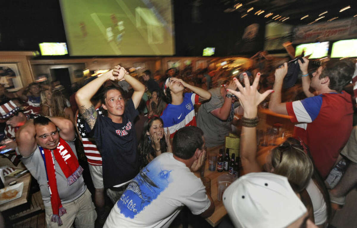 Craig Campbell, left, and Josh Trevino, second from left, react as the United States misses a chance to score in a World Cup soccer match between the U.S. and Belgium, Tuesday, July 1, 2014, in Jacksonville Beach, Fla. (AP Photo/The Florida Times-Union, Bob Mack)