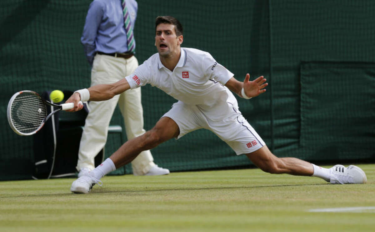 Novak Djokovic of Serbia plays a return during the men's singles quarterfinal match against Marin Cilic of Croatia at the All England Lawn Tennis Championships in Wimbledon, London, Wednesday July 2, 2014. (AP Photo/Ben Curtis)