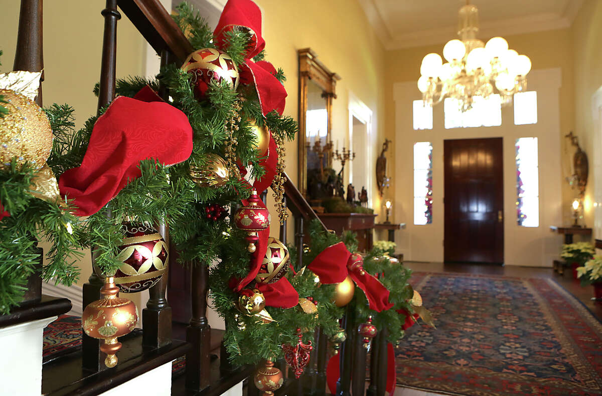 The banister to the staircase at The Texas Governor's Mansion in Austin is decorated with garland showing reds and golds.