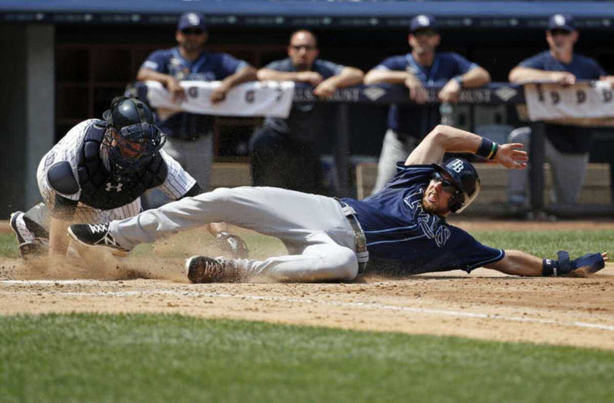 New York Yankees catcher Brian McCann (34) tags Tampa Bay Rays designated hitter Ben Zobrist out at the plate after Zobrist tried to score on Brandon Guyer's fifth-inning, RBI single in a baseball game at Yankee Stadium in New York, Wednesday, July 2, 2014. (AP Photo/Kathy Willens)