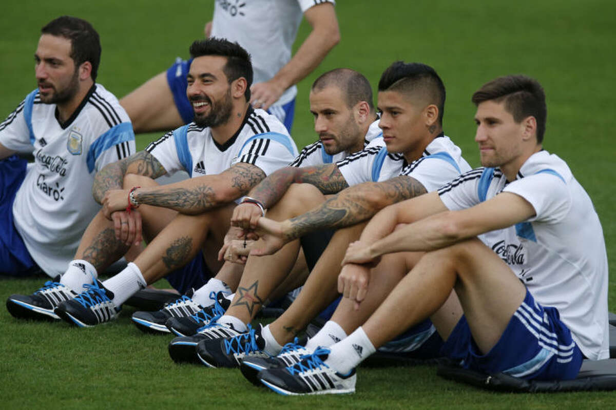 Argentine players sit during a training session in Vespesiano, near Belo Horizonte, Brazil, Wednesday, July 2, 2014. From right, Gonzalo Higuain, Ezequiel Lavezzi, Rodrigo Palacio, Marcos Rojo and Lucas Biglia. On Saturday, Argentina will face Belgium in their World Cup soccer match quarterfinal. (AP Photo/Victor R. Caivano)