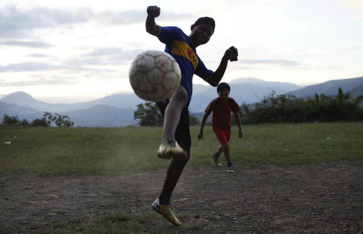 Young boys play soccer in field in Huarda Pata, Bolivia, Wednesday, July 2, 2014. The 2014 FIFA Soccer World Cup will enter the quarter finals stage on Friday with the top 8 teams of the world competing to make it to the final. (AP Photo/Juan Karita)