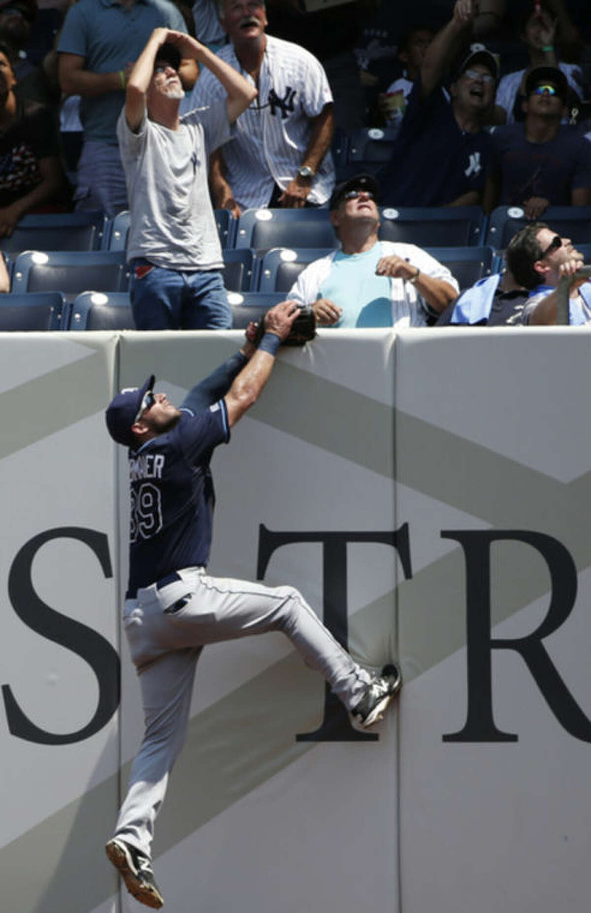 Tampa Bay Rays right fielder Kevin Kiermaier (39) climbs the outfield wall on Brian McCann's third inning home run in a baseball game at Yankee Stadium in New York, Wednesday, July 2, 2014. (AP Photo/Kathy Willens)