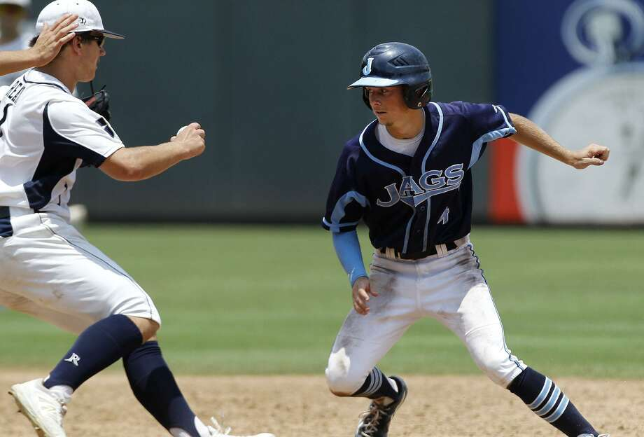 Johnson's Dalton Shuffield (right) looks to avoid a tag from Dallas Jesuit's Mark Ready during the UIL 6A state baseball championship game in Round Rock on June 11, 2016. Photo: Stephen Spillman /For The Express-News
