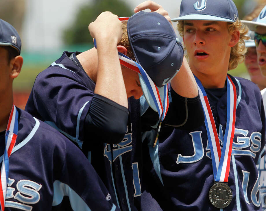 San Antonio Johnson's Joseph Haight, left, adjusts his silver medal with Chris Bialick after the Jaguars fell to Dallas Jesuit 6-2 in the Class 6A Championship. The final was Johnson's first. Photo: Stephen Spillman / Stephen Spillman