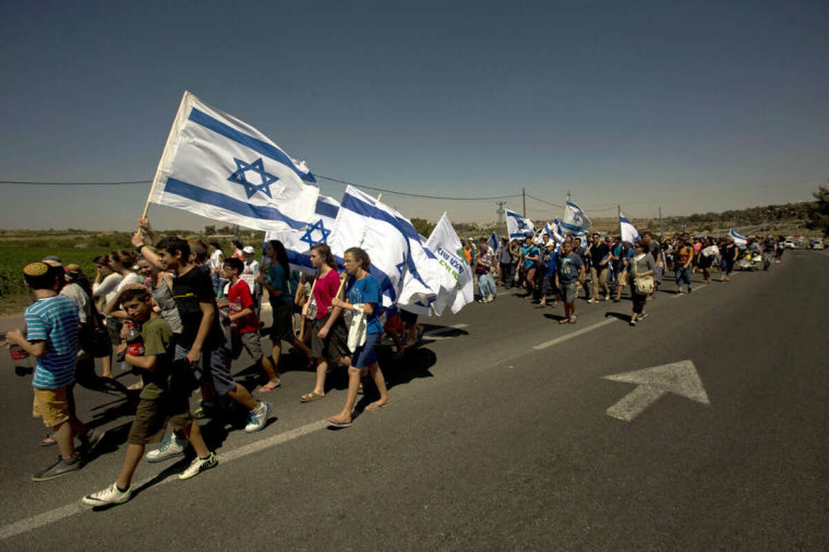 Israelis march on the road near where three missing teenagers were abducted, June 12, near the West Bank Jewish settlement of Alon Shvut , Tuesday, July 1, 2014. The Israeli military found the bodies of three missing teenagers just over two weeks after they were abducted in the West Bank ?- a grim discovery that ended a frantic search that led to Israel's largest ground operation in the Palestinian territory in nearly a decade and drew Israeli threats of retaliation. (AP Photo/Sebastian Scheiner)
