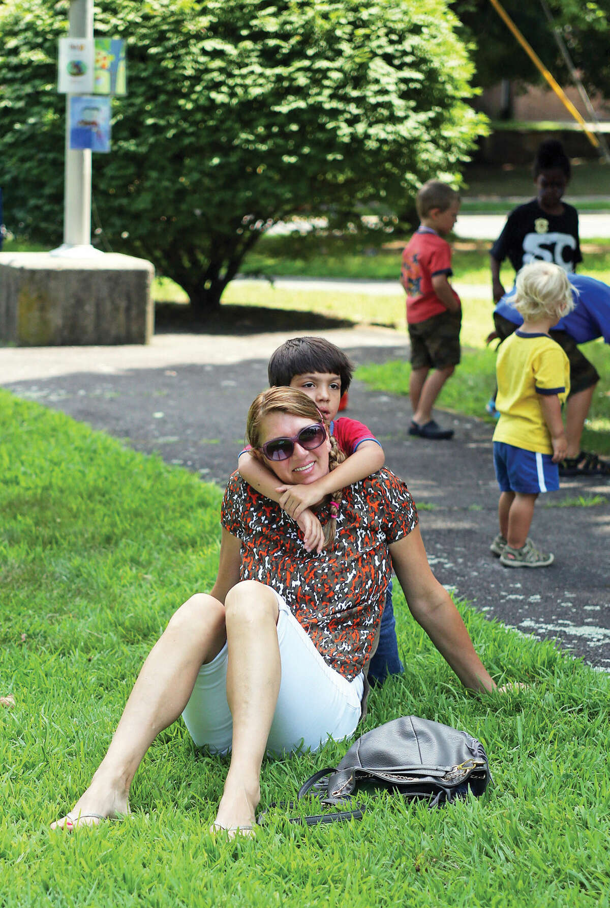 Luisa Soares and her son Nicholas, 5, watch live music during Norwalk's Citywide Summer Reading Challenge-Family Fun Festival at Union Park in Norwalk Saturday morning. Hour Photo / Danielle Calloway
