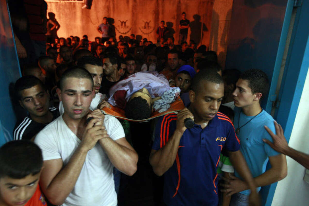 Palestinians carry the body of Yosuf abu Zaghah, 20, who was killed by the Israeli troops in the West Bank refugee camp of Jenin Early on Tuesday, July 1, 2014. Abu Zaghah, a Palestinian from the militant group Hamas was shot dead when he threw a grenade at forces carrying out an arrest raid in the West Bank hours after the discovery of the bodies of three Israeli teenagers who were abducted over two weeks ago, Israel's military said Tuesday. (AP Photo/Mohammed Ballas))