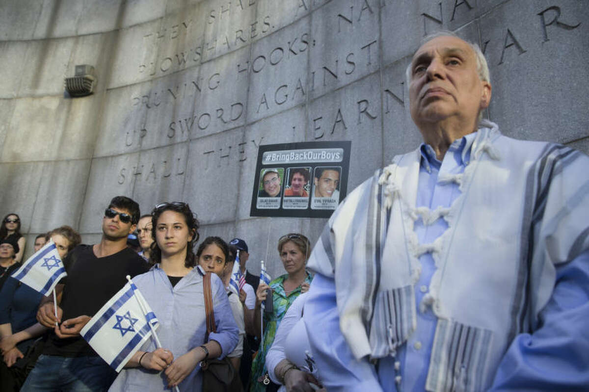 Rabbi Avi Weiss, right, stands with demonstrators during a memorial service outside the United Nations headquarters for the three missing Israeli teenagers whose bodies were found by the Israeli military on Monday, just over two weeks after they went missing in the West Bank, Monday, June 30, 2014, in New York. The discovery culminated the feverish search that led to Israel's largest ground operation in the Palestinian territory in nearly a decade and drew Israeli threats of retaliation. (AP Photo/John Minchillo)
