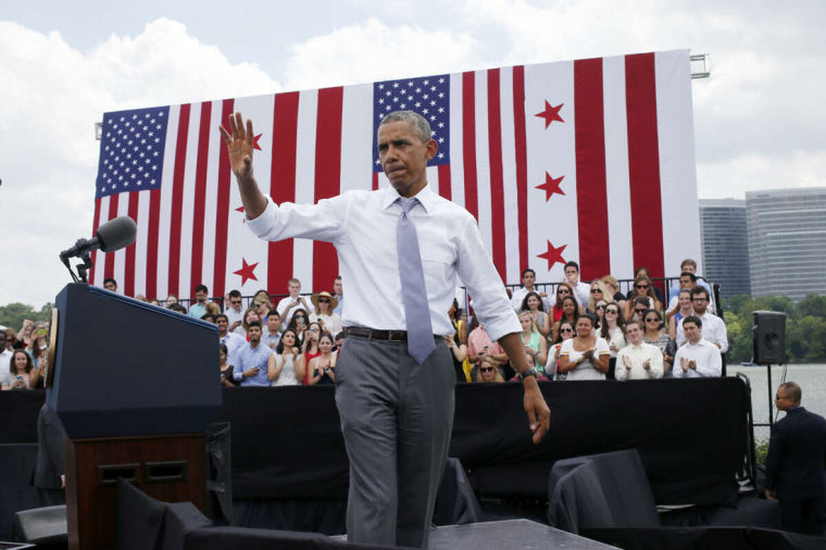 President Barack Obama waves after his remarks about transportation and the economy, Tuesday, July 1, 2014, at Georgetown Waterfront Park in Washington. The president said 700,000 jobs could be at risk next year if Congress doesn't quickly agree on how to pay for highway and transit programs. (AP Photo/Charles Dharapak)
