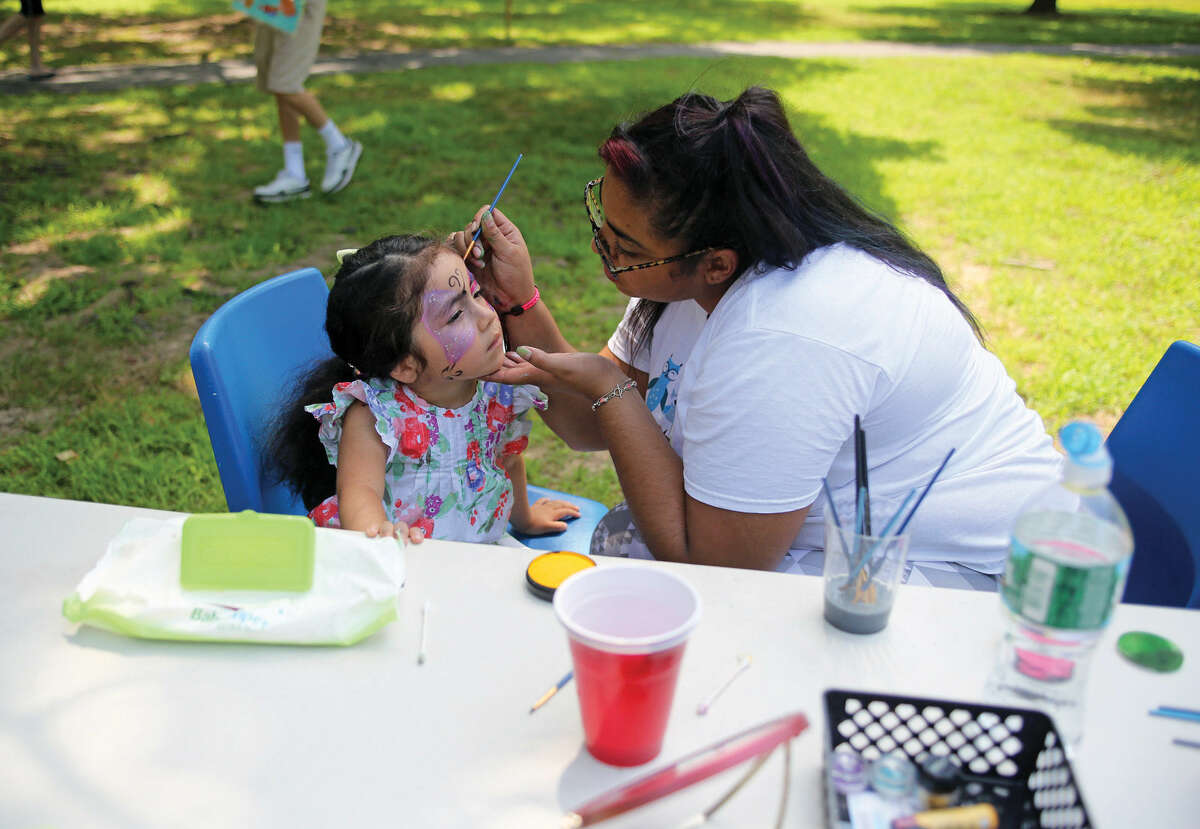 Maria Jose Aquino, 3 1/2, gets her face painted by China Perez-Brown during Norwalk's Citywide Summer Reading Challenge-Family Fun Festival at Union Park in Norwalk Saturday morning. Hour Photo / Danielle Calloway