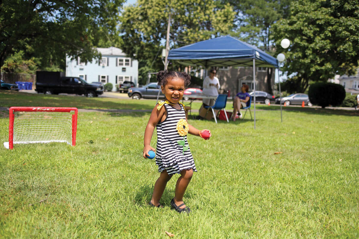 Shanell Alexis, 2 1/2, plays in the grass during Norwalk's Citywide Summer Reading Challenge-Family Fun Festival at Union Park in Norwalk Saturday morning. Hour Photo / Danielle Calloway