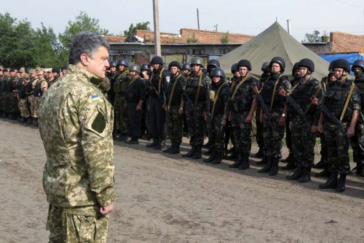 In this photo taken on Friday, June 20, 2014 in Izyum close to Slovyansk, eastern Ukraine, Ukrainian President Petro Poroshenko visits troops. Poroshenko in a televised address early Tuesday, July 1, 2014, said he was abandoning a unilateral cease-fire in the conflict with pro-Russian separatists and sending military forces back on the offensive after talks with Russia and European leaders failed to start a broader peace process. The cease-fire expired at 10 p.m. Monday.(AP Photo/Mykhailo Markiv, Pool)
