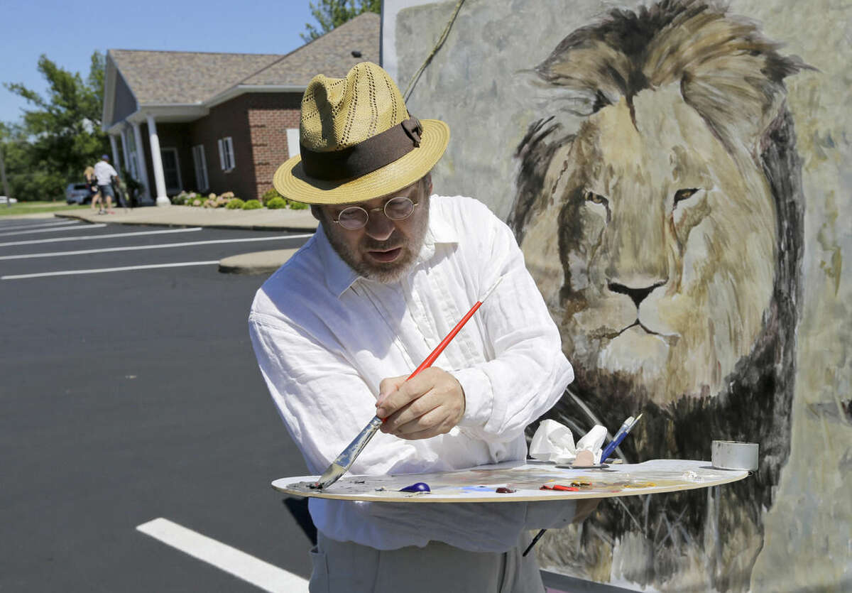 Mark Balma works on a mural of Cecil the lion outside Dr. Walter James Palmer's dental office in Bloomington, Minn., Wednesday, July 29, 2015. Authorities allege that Palmer paid $50,000 to track and kill Cecil, a protected lion, just outside Hwange National Park in Zimbabwe. (AP Photo/Ann Heisenfelt)