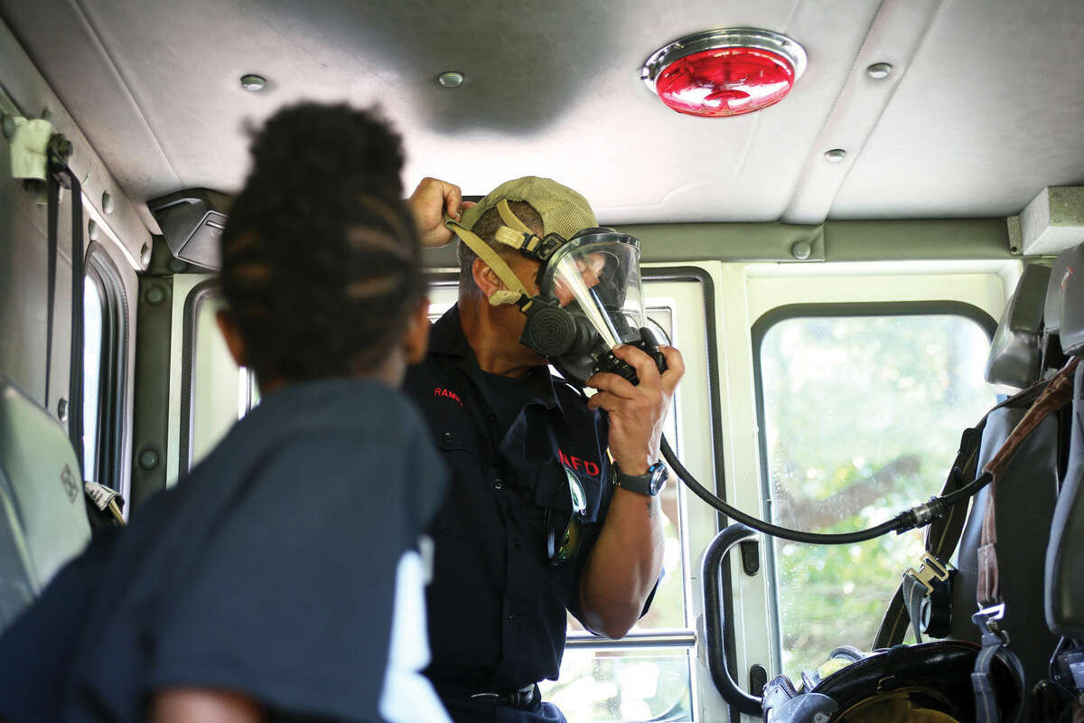 Zoe Re Ragin, 5, learns about fire safety inside a firetruck during Norwalk's Citywide Summer Reading Challenge-Family Fun Festival at Union Park in Norwalk Saturday morning. Hour Photo / Danielle Calloway