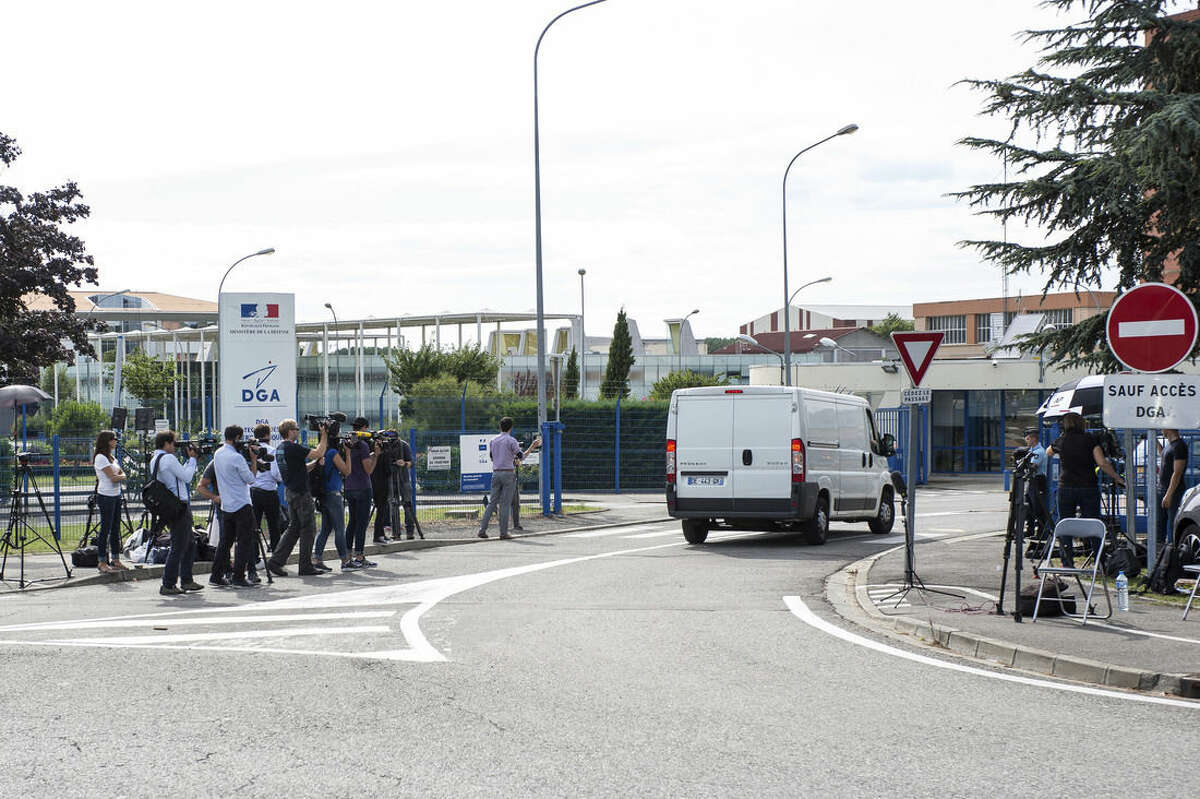 Members of the media watch as a white van, accompanied by police motorcycles and a police car transporting what is believed to be debris from a Boeing 777 plane that washed up on an Indian Ocean island, arrives at Direction Generale de L'armement (DGA) facilities in Blagnac , near Toulouse, south-western France, Saturday, Aug. 1, 2015. A piece of plane wing that could be from missing Malaysia Airlines Flight 370 arrived Saturday in Toulouse, France, for inspection by military aviation experts.The 6-foot-long part, wrapped in a box and shipped as cargo, was flown from the small island of Reunion, near Madagascar. (AP Photo/Fred Lancelot)