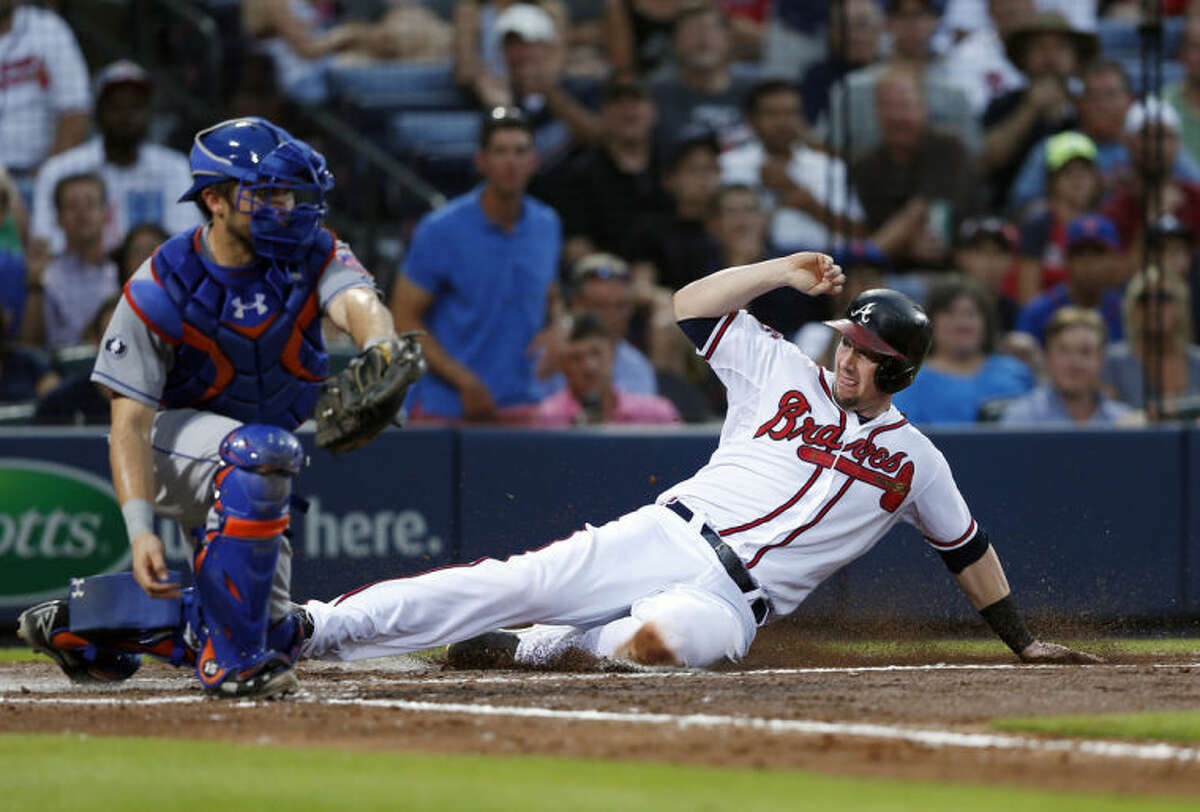 Atlanta Braves' Chris Johnson (23) scores on a Mike Minor base hit as New York Mets catcher Travis d'Arnaud (15) handles the late throw in the fourth inning of a baseball game in Atlanta, Tuesday, July 1, 2014. (AP Photo/John Bazemore)