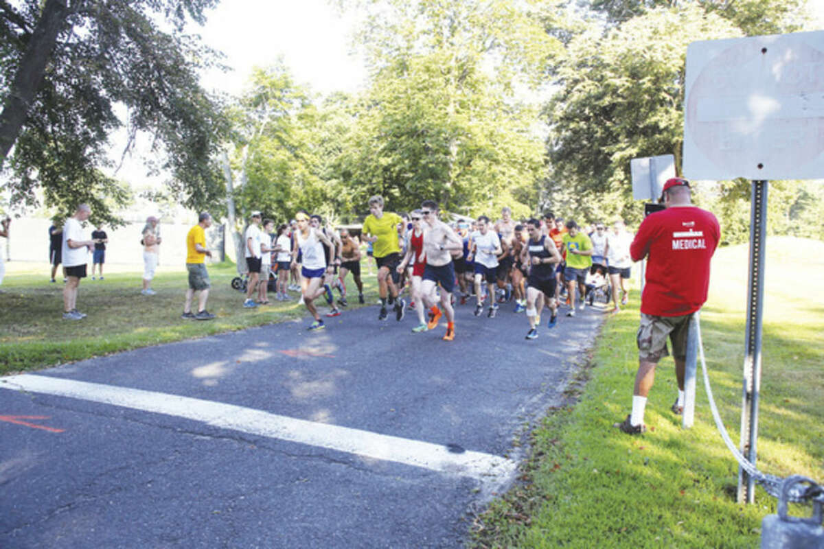 Hour photo/Danielle Calloway Runners start the Westport Road Runners 4.7 mile road race at Longshore Country Club in Westport on Saturday morning.