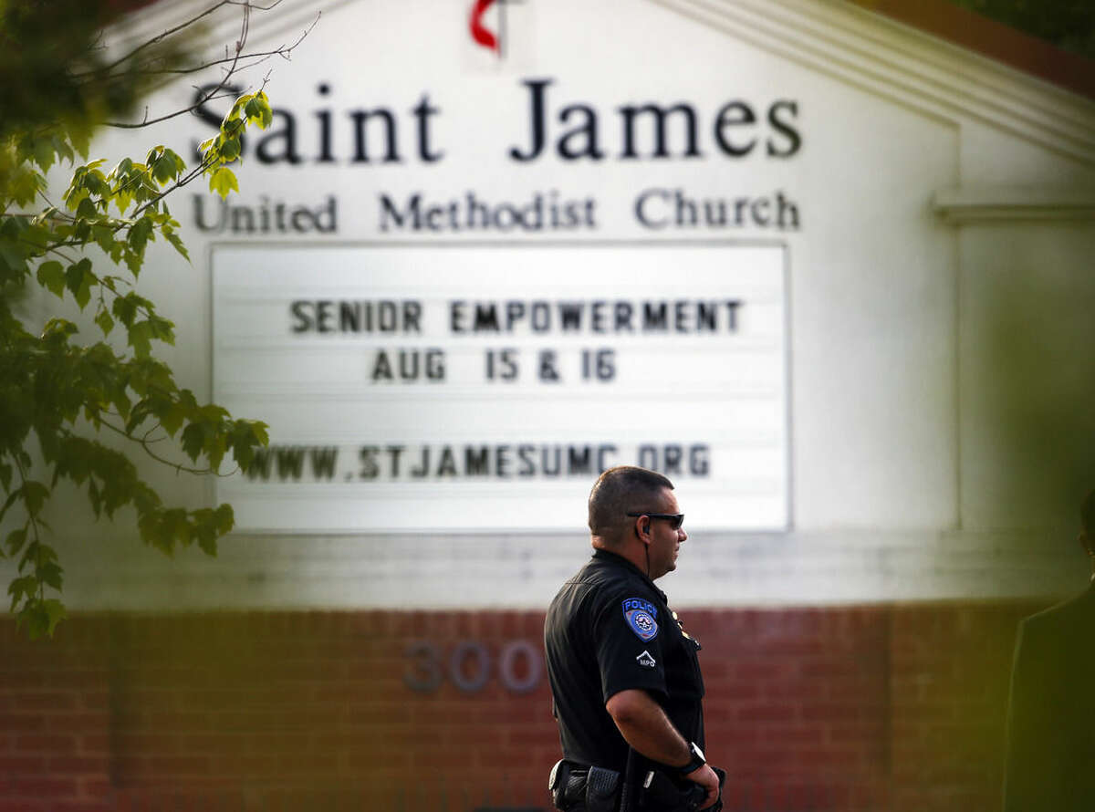 A police officer stands guard at the entrance to St. James United Methodist Church before funeral services for Bobbi Kristina Brown Saturday, Aug. 1, 2015, in Alpharetta, Ga. Brown, the only child of Whitney Houston and R&B singer Bobby Brown, died in hospice care July 26, about six months after she was found face-down and unresponsive in a bathtub in her suburban Atlanta townhome. (AP Photo/John Bazemore)