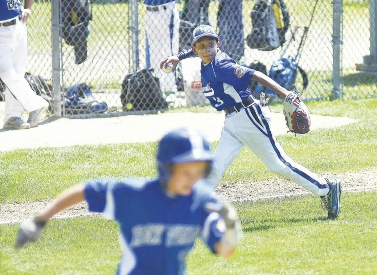Hour photo/John Nash Norwalk 11s' third baseman Jayden Gonzalez, top, comes up firing to first after playing Raynham hitter Joey Leclerc's bunt bare-handed in the second inning of Saturday's Cal Ripken 11-year-old New England Regional Tournament at Keyes Field in Dover, N.H. on Saturday.