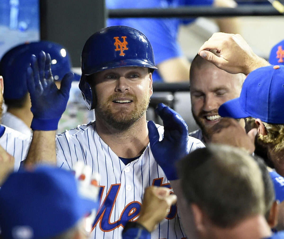 New York Mets' Lucas Duda is congratulated by teammates in the dugout after hitting his second home run of a baseball game against the Washington Nationals in the seventh inning at Citi Field on Saturday, Aug. 1, 2015, in New York. (AP Photo/Kathy Kmonicek)