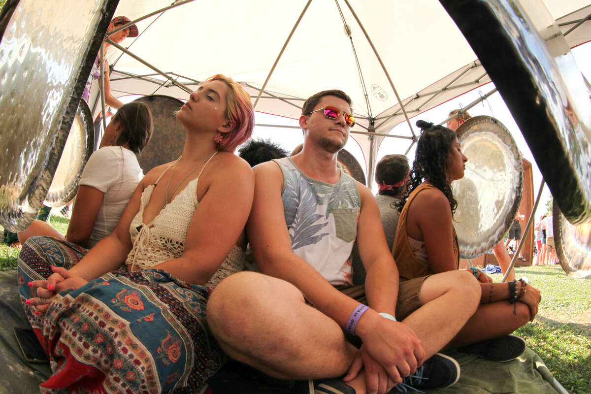 Hour photo/Chris Palermo. Festival goers sit in a gong circle at the Gathering of the Vibes festival at Seaside Park in Bridgeport Saturday.