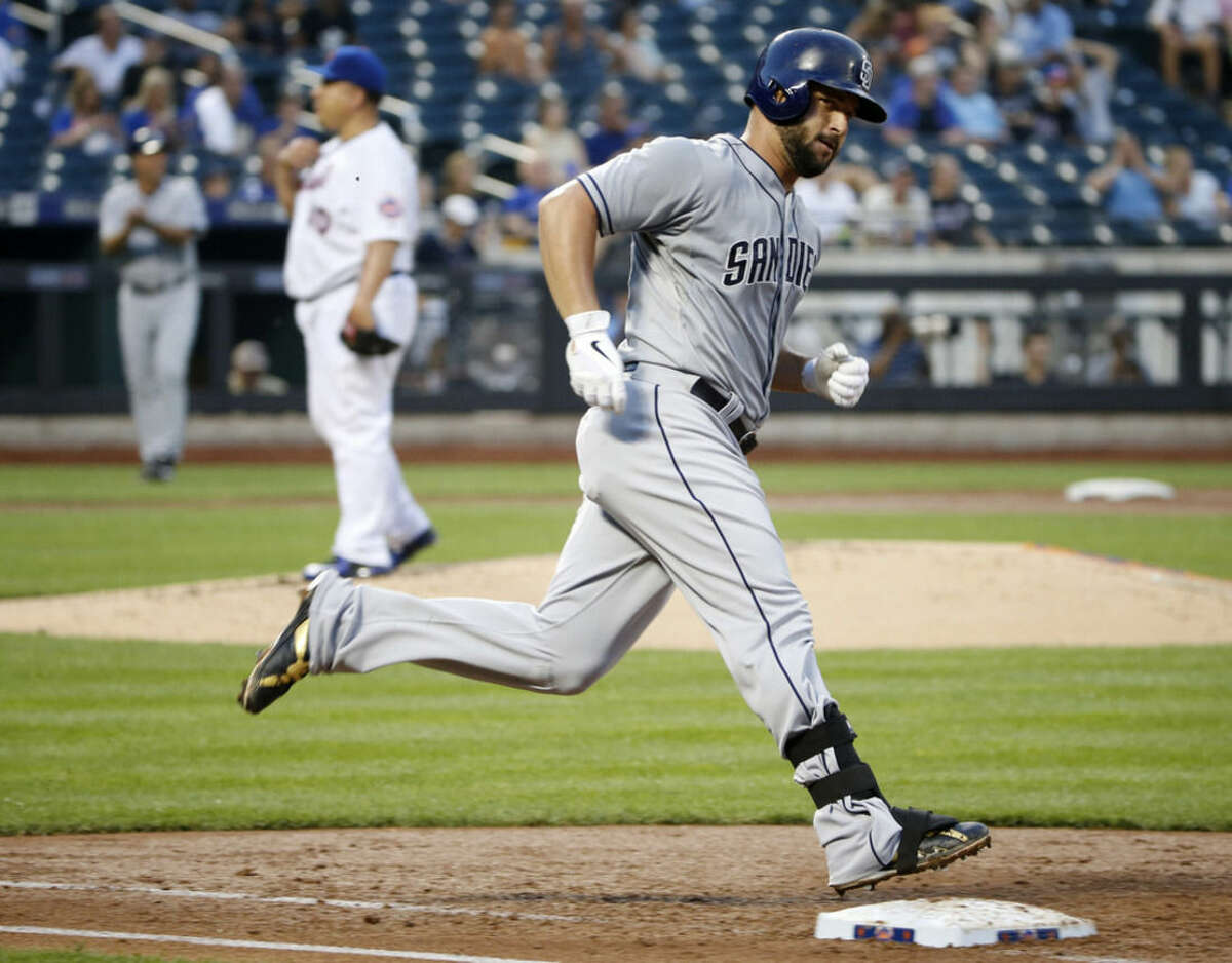 San Diego Padres Yonder Alonso, right, runs over first base after hitting a third-inning solo home run off New York Mets starting pitcher Bartolo Colon, center, in a baseball game in New York, Wednesday, July 29, 2015. (AP Photo/Kathy Willens)