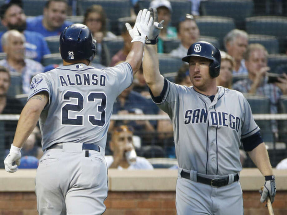 San Diego Padres on-deck batter Jedd Gyorko, right, greets teammate Yonder Alonso (23) after Alonso's third- inning solo home run in a baseball game against the New York Mets in New York, Wednesday, July 29, 2015. (AP Photo/Kathy Willens)