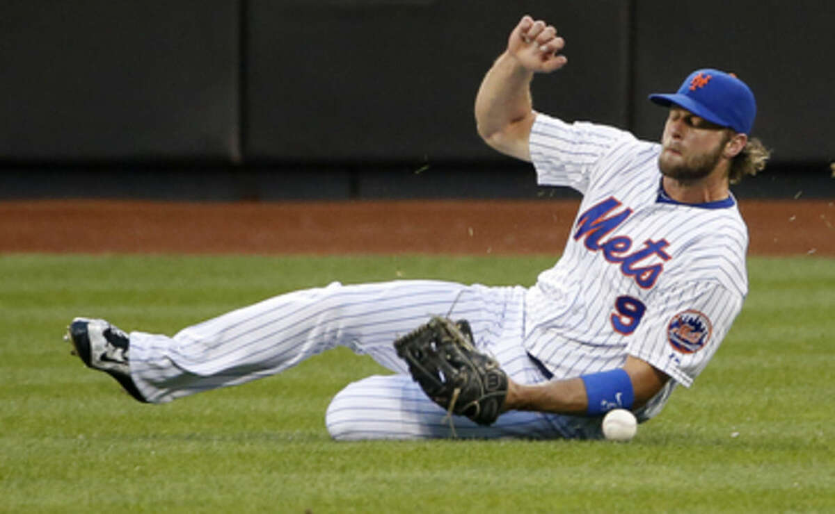 New York Mets center fielder Kirk Nieuwenhuis (9) comes up short while sliding to field a third-inning single hit by San Diego Padres' Austin Hedges in a baseball game in New York, Wednesday, July 29, 2015. (AP Photo/Kathy Willens)