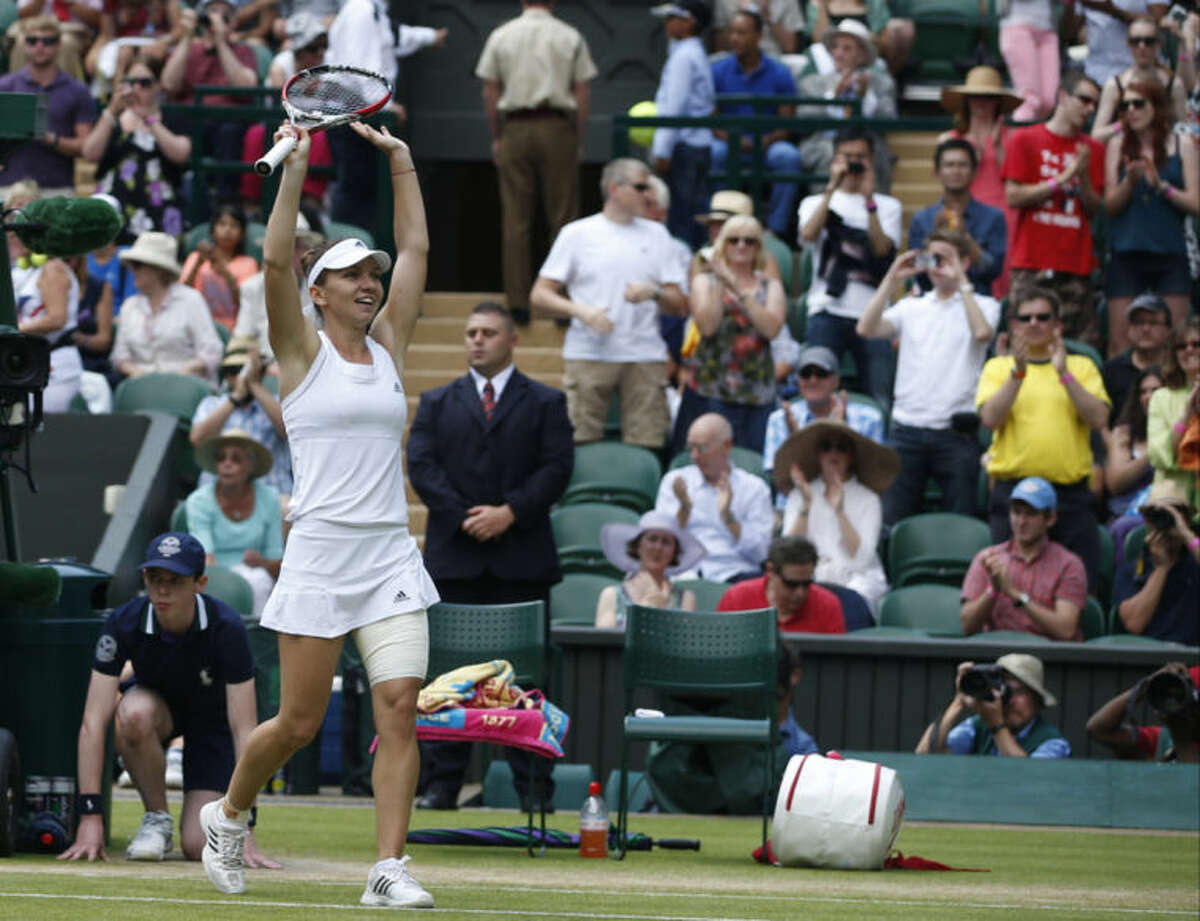 Simona Halep of Romania waves to the crowd after defeating Sabine Lisicki of Germany in their women's quarterfinal their match at the All England Lawn Tennis Championships in Wimbledon, London, Wednesday, July 2, 2014. (AP Photo/Pavel Golovkin)