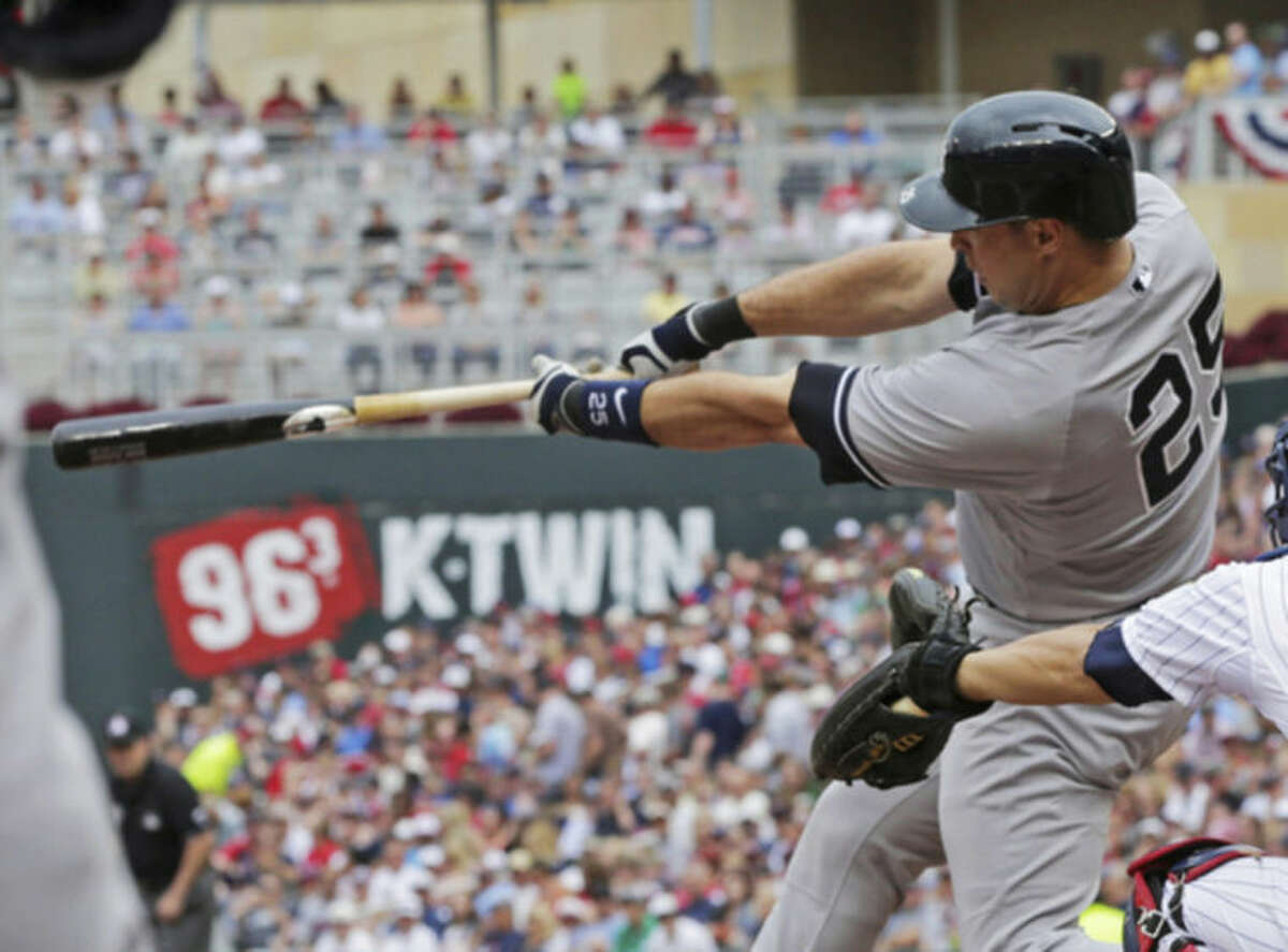 New York Yankees' Mark Teixeira hits an RBI double off Minnesota Twins pitcher Kyle Gibson in the first inning of a baseball game, Friday, July 4, 2014, in Minneapolis. (AP Photo/Jim Mone)