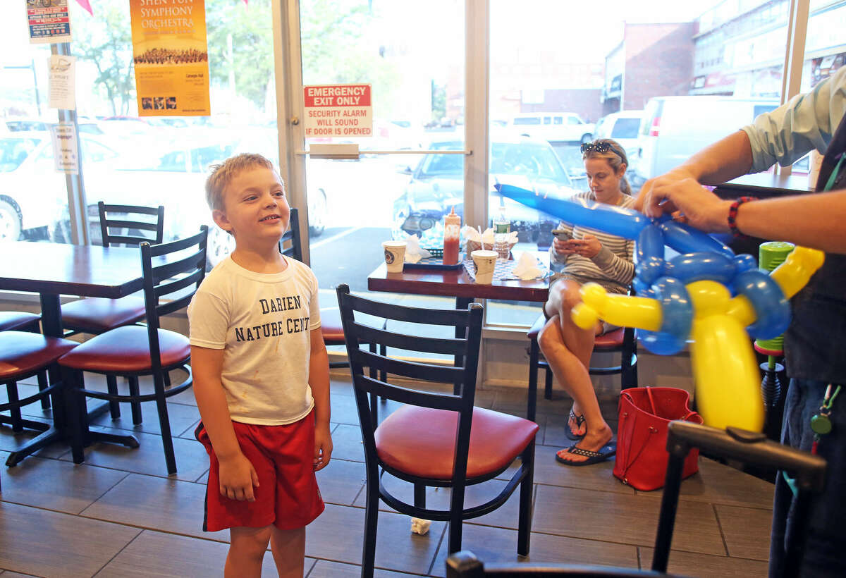 Balloons By Anthony makes a balloon animal for Colin Anderson, 5, during Balloon Night at The Dairy Inn on Hope Street.