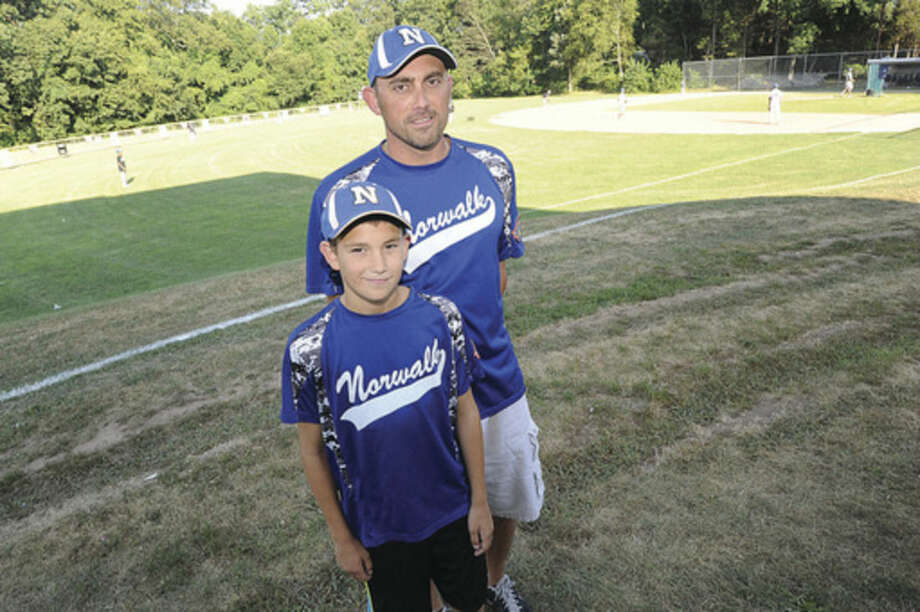 Hour photo/Matthew VinciCoach Mark Boccanfuso and his son Ben at Devine Field in Norwalk. Together, the father and son team have helped the Norwalk Cal Ripken 11-year-old All-Stars win the state championship, advancing to the New England Regional championship tournament in Dover, N.H.
