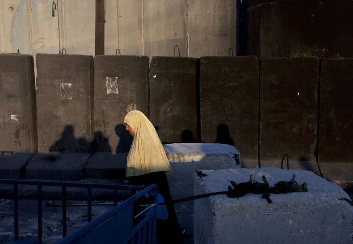 A Palestinian woman walks by the Israeli separation barrier on her way to Jerusalem through the Qalandia security checkpoint, on the outskirts of the West Bank city of Ramallah, Friday, July 4, 2014. (AP Photo/Nasser Nasser)